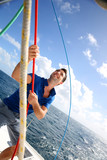 Young man lifting the sail of catamaran during cruising