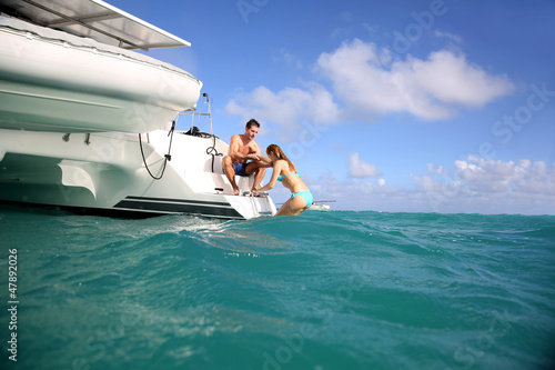 Young people swimming in the sea next to sailboat