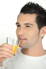 Man drinking a glass of orange juice