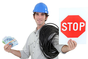 Electrician holding stop sign and cash