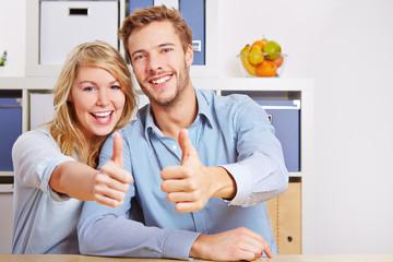 Paar hält Daumen hoch im Wohnzimmer