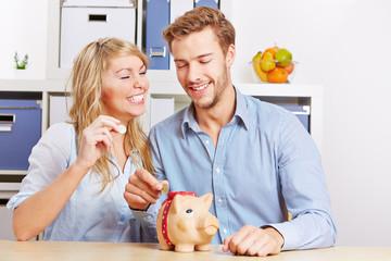Paar steckt Münzen in Sparschwein