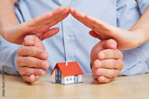 Hände bilden Dach über Haus