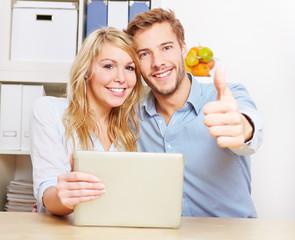 Paar mit Tablet Computer hält Daumen hoch