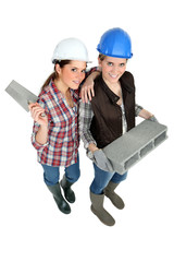 two female builders posing