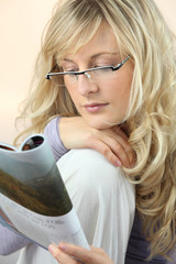 Attractive woman in glasses reading a magazine