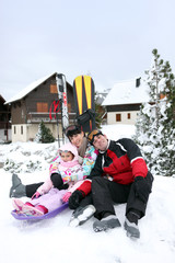 Family of skiers sat by chalet