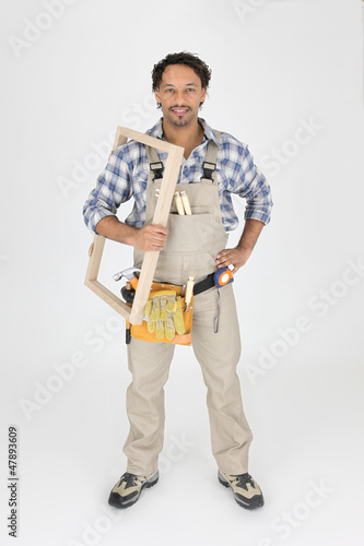 A carpenter holding a frame