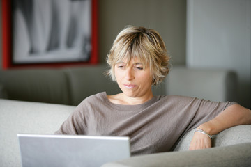 Woman using a laptop on the sofa
