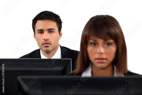 Office workers sitting at desktop computers
