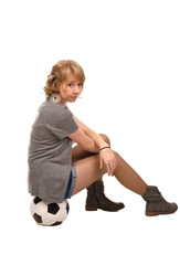 Stylish young girl sitting on a soccer ball