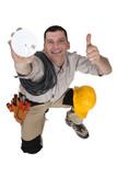 Tradesman holding up a smoke detector poster