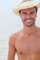 Man stood on the beach wearing straw hat