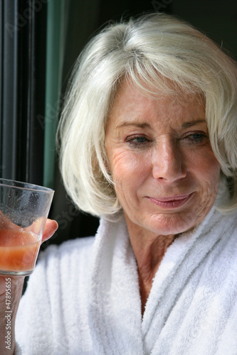 Elderly lady drinking fruit juice