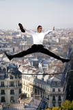 Businessman jumping for joy on a tightrope