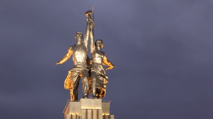 Monument to worker and collective farmer stands against night