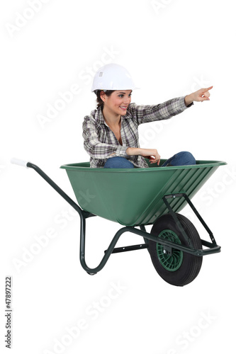 Female tradesperson sitting in a wheelbarrow