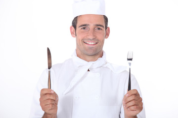 Chef in uniform holding a knife and fork