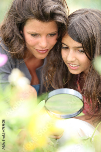 Mother and daughter with a magnifying glass