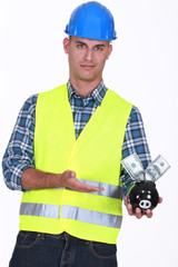 Manual worker holding piggy-bank