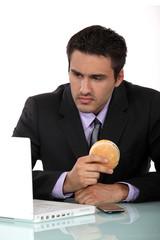 Man sat at his desk eating hamburger