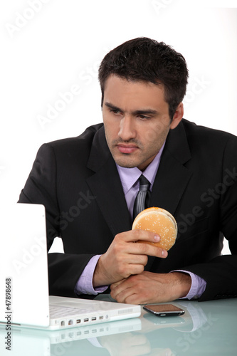 Man sat at his desk eating hamburger