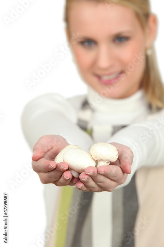 Blonde woman showing bunch of mushrooms
