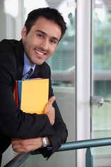 Smiling businessman holding files
