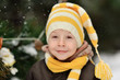 portrait of a boy in a cap on a background of winter trees