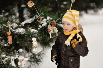 in the forest boy decorates a Christmas tree toys