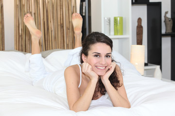 Happy woman lying in bed