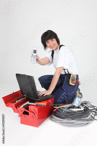 Female labourer with tools and telephone