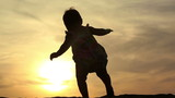 Silhouette of adorable baby girl walking over sunset