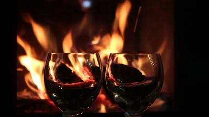 Zwei Weingläser vor Kaminfeuer