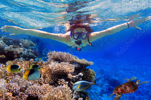Leinwanddruck Bild Young women at snorkeling in the tropical water