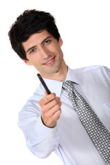 Businessman holding out a pen