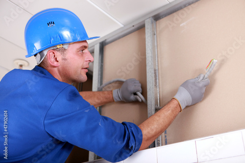 technician in action, installing wires in a wall