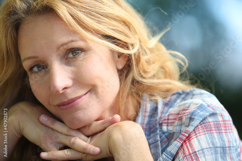 Blond woman resting chin on hands