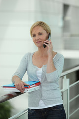 Businesswoman on mobile telephone holding folders