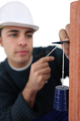 craftsman taking measurements with a cord