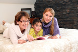 Mother, daughter and granddaughter reading book