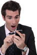 Shocked businessman reading text message