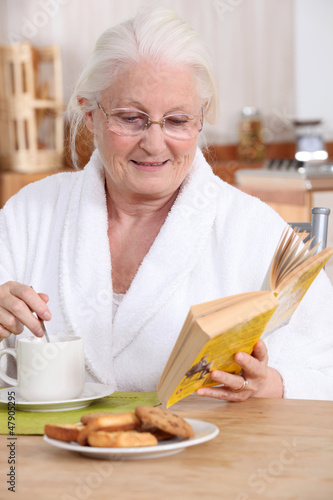 Elderly lady enjoying tea and biscuits