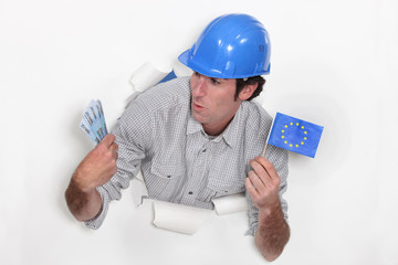 Tradesman holding a European Union flag and money
