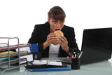 Woman eating a burger at her desk