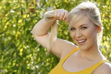 Blonde hübsche Frau zieht an ihren langen Haaren