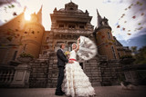 newlyweds are hugging near the ancient castle