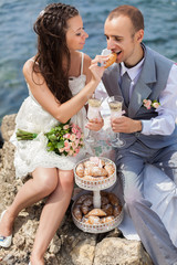bride and groom celebrating on cliffs by the sea with champagne