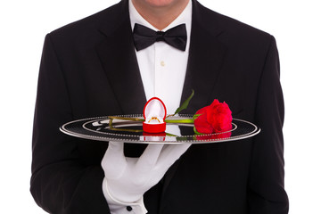 Butler with engagement ring and red rose