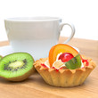 cake with fruit, kiwi fruit and a cup of tea